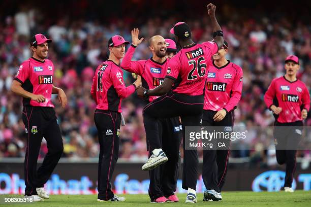 Nathan Lyon of the Sixers celebrates with Carlos Brathwaite of the Sixers after taking the wicket of Sam Heazlett of the Heat during the Big Bash...