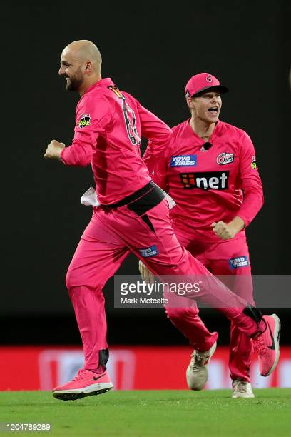 Nathan Lyon of the Sixers celebrates with Steve Smith of the Sixers after taking the wicket of Marcus Stoinis of the Stars during the Big Bash League...