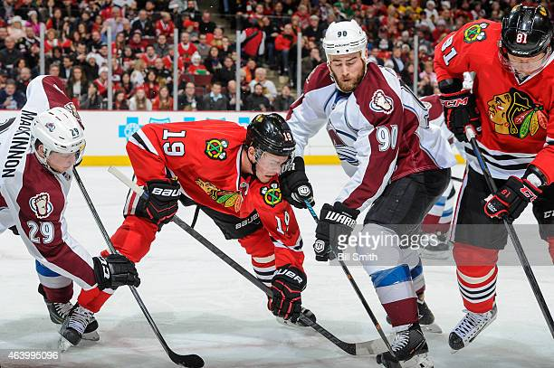 Nathan MacKinnon and Ryan O'Reilly of the Colorado Avalanche work to get the puck against Jonathan Toews and Marian Hossa of the Chicago Blackhawks...