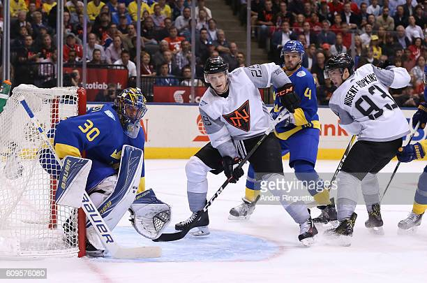 Nathan MacKinnon of Team North America battles for position with Niklas Hjalmarsson in front of Henrik Lundqvist of Team Sweden during the World Cup...