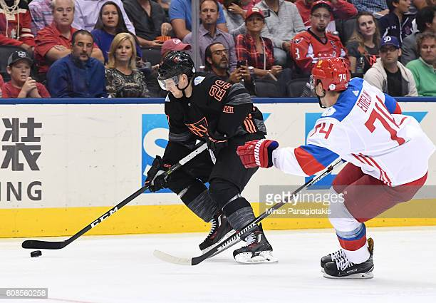 Nathan MacKinnon of Team North America stickhandles the puck with Alexei Emelin of Team Russia chasing during the World Cup of Hockey 2016 at Air...