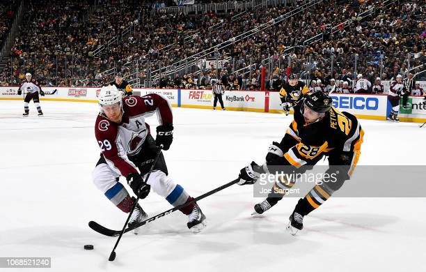 Nathan MacKinnon of the Colorado Avalanche and Marcus Pettersson of the Pittsburgh Penguins battle for the puck at PPG Paints Arena on December 4...