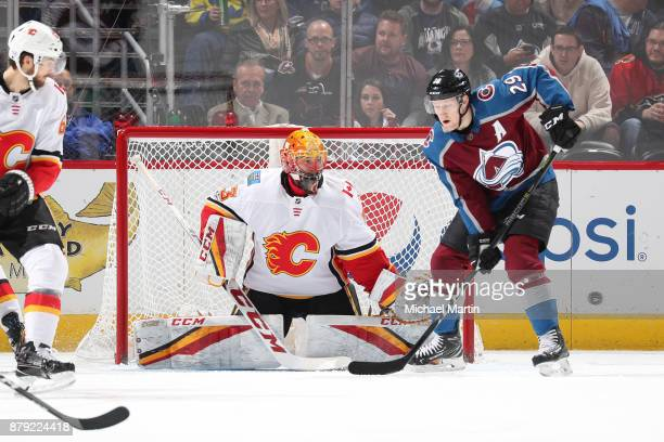 Nathan MacKinnon of the Colorado Avalanche attempts to deflect the puck past goaltender David Rittich of the Calgary Flames at the Pepsi Center on...