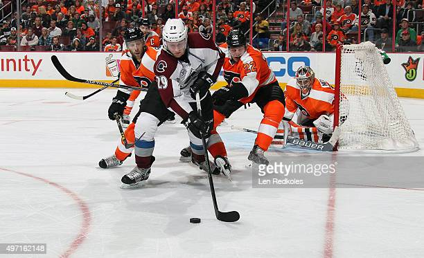 Nathan MacKinnon of the Colorado Avalanche battles for the loose puck against Luke Schenn and Nick Schultz of the Philadelphia Flyers in front of...