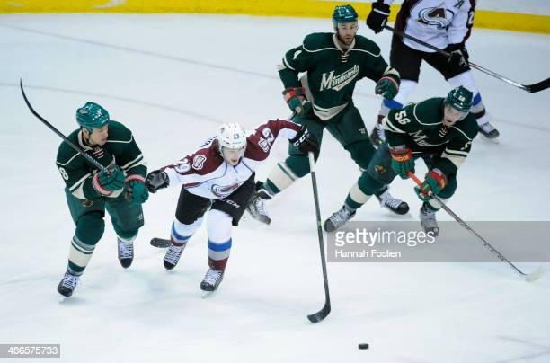 Nathan MacKinnon of the Colorado Avalanche controls the puck against Cody McCormick Clayton Stoner and Erik Haula of the Minnesota Wild during the...