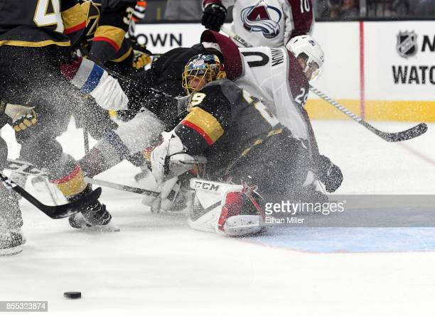 Nathan MacKinnon of the Colorado Avalanche falls over MarcAndre Fleury of the Vegas Golden Knights after he made a save during the first period of...