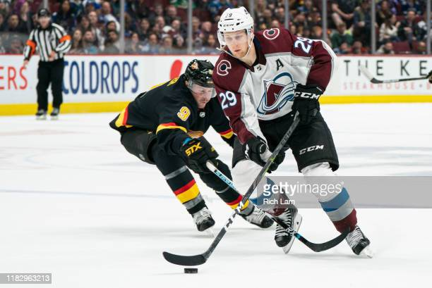 Nathan MacKinnon of the Colorado Avalanche gets around J.T. Miller of the Vancouver Canucks while on his way to scoring the game winning goal in...