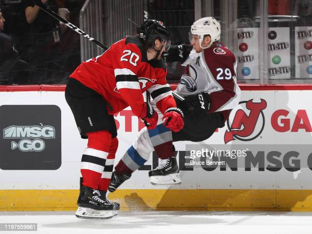 Nathan MacKinnon of the Colorado Avalanche is checked by Blake Coleman of the New Jersey Devils during the second period at the Prudential Center on...