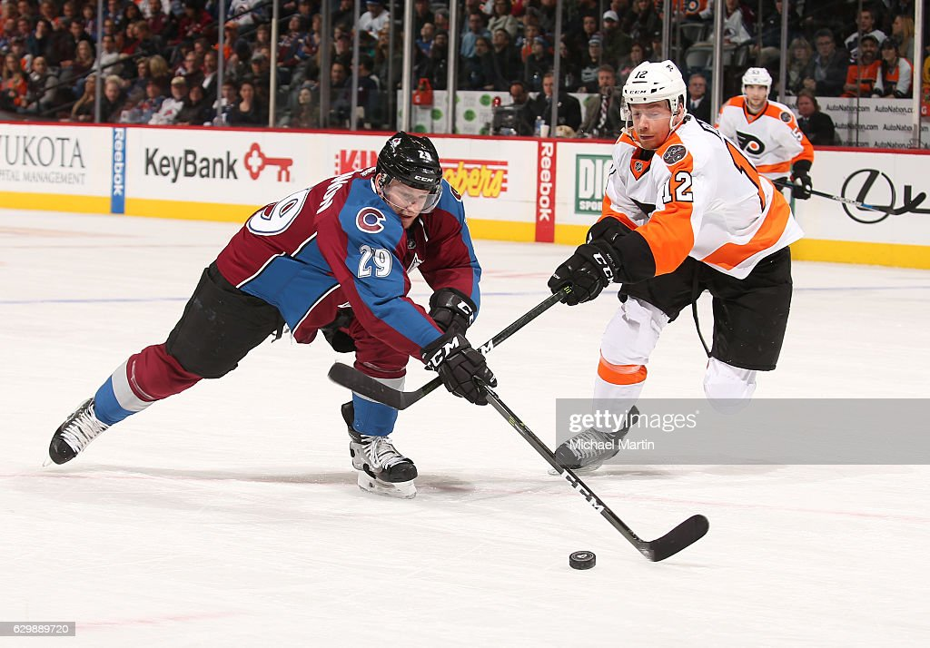 Nathan MacKinnon #29 of the Colorado Avalanche skates against Michael Raffl #12 of the Philadelphia Flyers at the Pepsi Center on December 14, 2016 in Denver, Colorado.