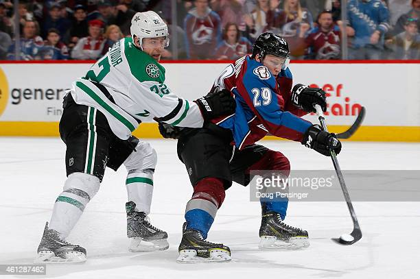 Nathan MacKinnon of the Colorado Avalanche takes a shot as Colton Sceviour of the Dallas Stars defends at Pepsi Center on January 10 2015 in Denver...