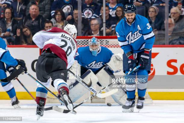 Nathan MacKinnon of the Colorado Avalanche takes a shot from the point as Dustin Byfuglien of the Winnipeg Jets defends during second period action...