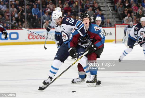 Nathan MacKinnon of the Colorado Avalanche takes an elbow to the face from Andrew Ladd of the Winnipeg Jets at the Pepsi Center on March 10 2014 in...
