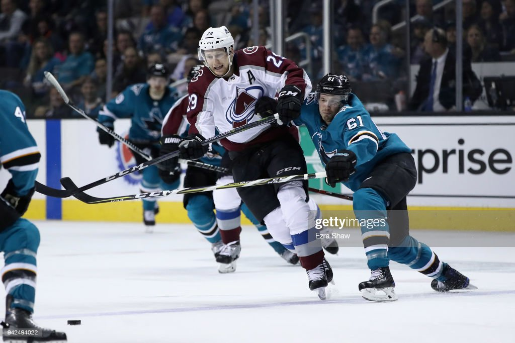 Nathan MacKinnon #29 of the Colorado Avalanche tries to skate away from Justin Braun #61 of the San Jose Sharks at SAP Center on April 5, 2018 in San Jose, California.