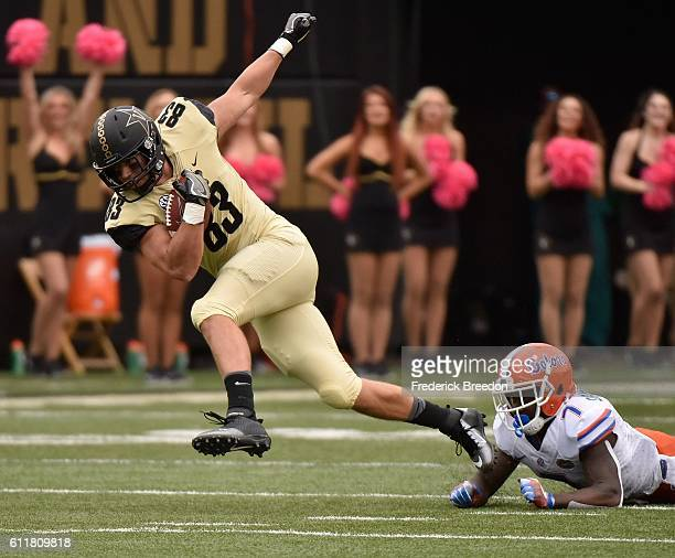 Nathan Marcus of the Vanderbilt Commodores is tackled by Duke Dawson of the Florida Gators during the first half at Vanderbilt Stadium on October 1...