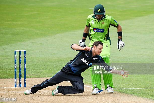 Nathan McCullum of New Zealand fields off his own bowling while MisbahulHaq of Pakistan looks on during the One Day International match between New...