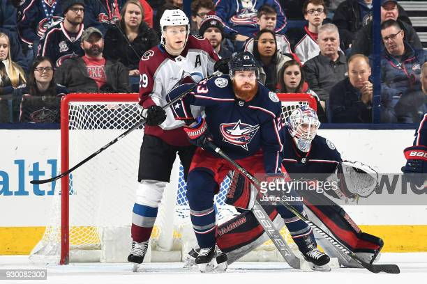 Nathan McKinnon of the Colorado Avalanche and Ian Cole of the Columbus Blue Jackets battle for position in front of goaltender Joonas Korpisalo of...