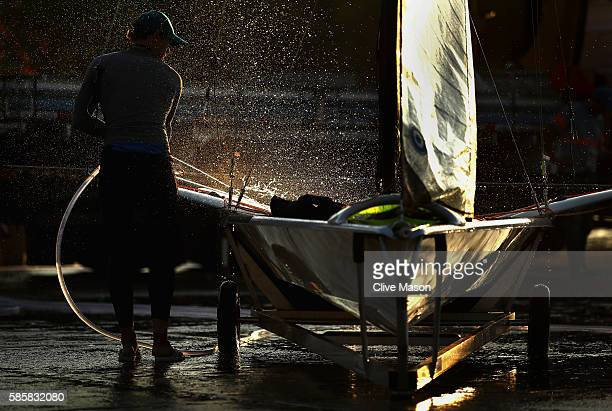 Nathan Outteridge of Australia washes down his 49er skiff after practice ahead of the Rio 2016 Olympic Games at the Marina da Gloria on August 4,...