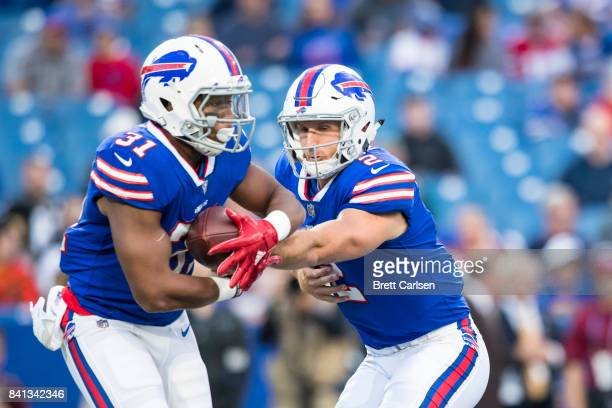 Nathan Peterman hands off the ball to Jonathan Williams of the Buffalo Bills during the first quarter of a preseason game against the Detroit Lions...