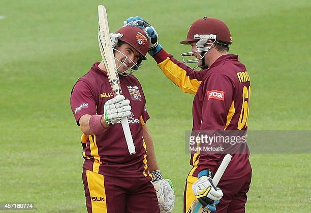 Nathan Reardon of Queensland celebrates with team mate Peter Forrest after scoring a half century during the Matador BBQs Cup match between...