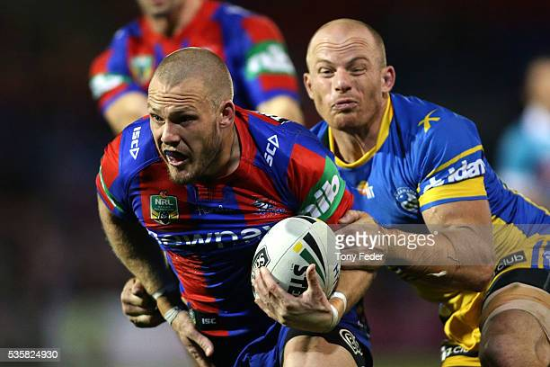 Nathan Ross of the Knights is tackled by Beau Scott of the Eels during the round 12 NRL match between the Newcastle Knights and the Parramatta Eels...