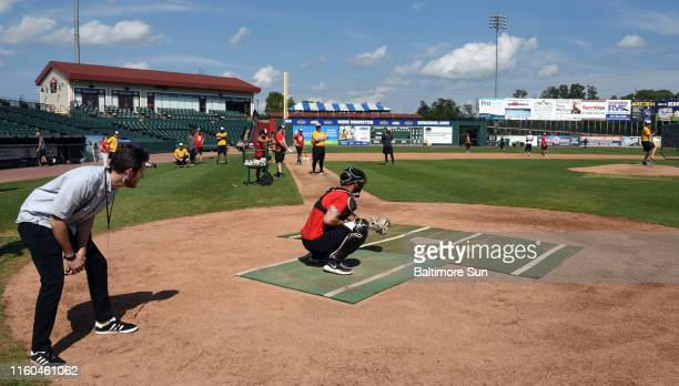 Nathan Ruiz, who covers baseball for the Baltimore Sun, stands behind home plate as he tries the new roboump/Automated Balls and Strikes radar...