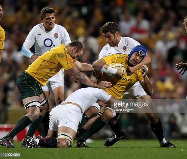 Nathan Sharpe of the Australian Wallabies is tackled by Tom Palmer and Nick Easter during the Cook Cup Test match between the Australian Wallabies...