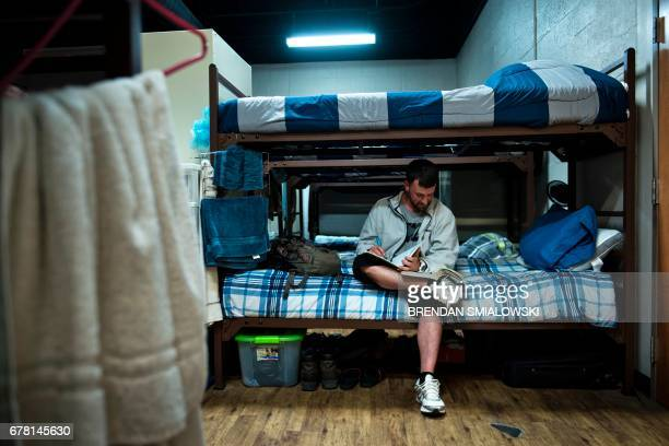 Nathan Sparks sits in his dorm while working on recovery program homework while staying at Recovery Point on April 19, 2017 in Huntington, West...