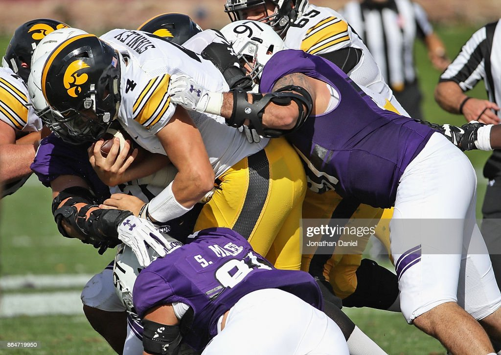 Nathan Stanley #4 of the Iowa Hawkeyes is dropped for a loss by (L-R) Alex Miller #95, Sam Miller #91, and Joe Gaziano #97 of the Northwestern Wildcats at Ryan Field on October 21, 2017 in Evanston, Illinois. Northwestern defeated Iowa 17-10 in overtime.