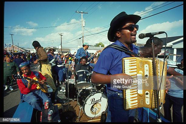 Nathan Williams sings and plays the accordion with his zydeco band as they ride on the back of a truck in a Mardi Gras parade on the streets of St....