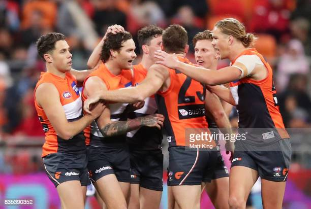 Nathan Wilson of the Giants celebrates with team mates after kicking a long range goal during the round 22 AFL match between the Greater Western...