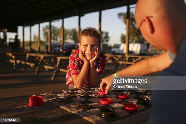 Nathan Woessner looks at his mother Faith Woessner while playing checkers with his dad Greg Woessner in Washington Park on September 6 in Michigan...