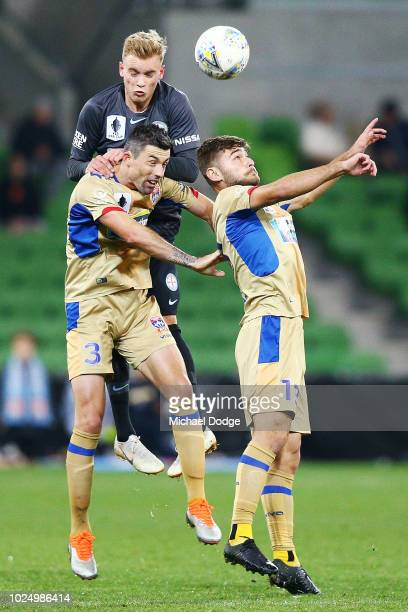 Nathaniel Atkinson of the City heads the ball over Jason Hoffman and Ivan Vujica of the Jets during the FFA Cup round of 16 match between Melbourne...