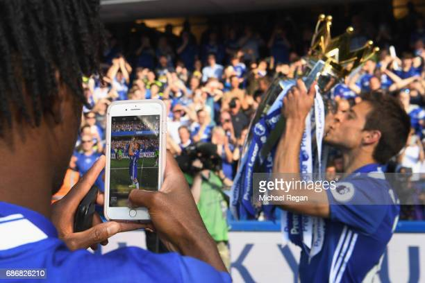 Nathaniel Chalobah of Chelsea takes a picture of team mate Cesar Azpilicueta and the Premier League Trophy on a phone after the Premier League match...