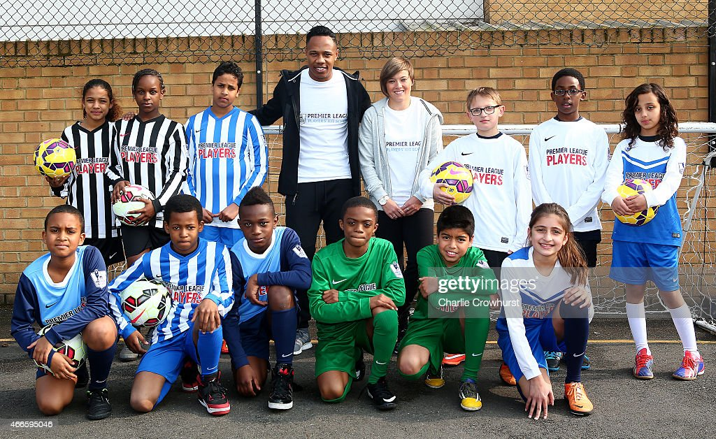 Nathaniel Clyne (R) and Fran Kirby pose for a photograph with the school children during the Premier League Players Kit Scheme Launch at Allen Edward Primary School on March 17, 2015 in London, England.
