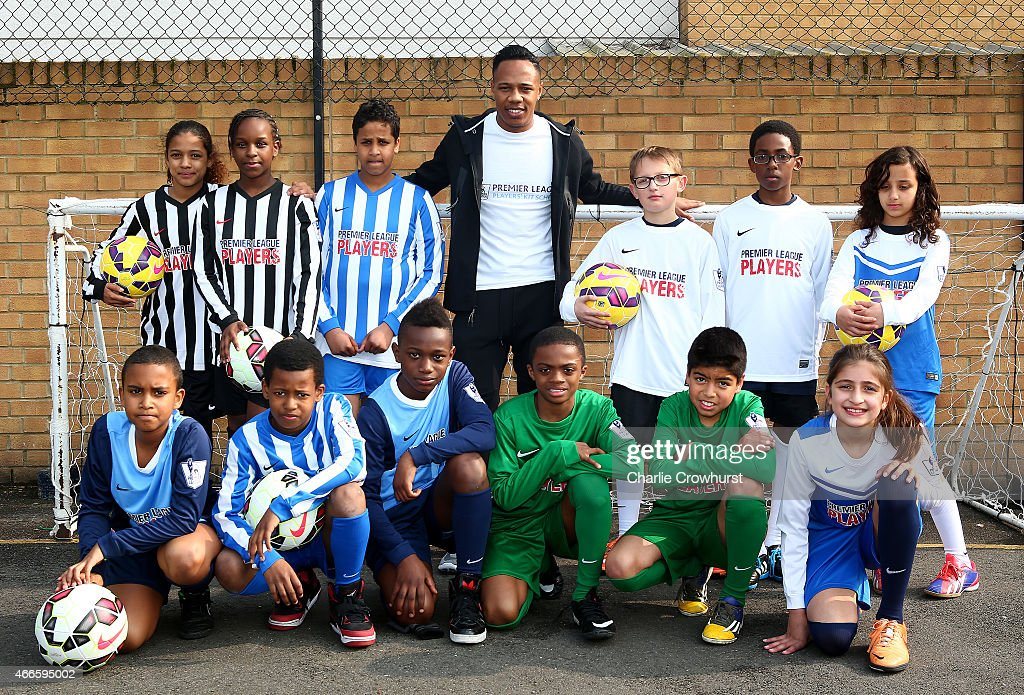 Nathaniel Clyne poses for a photograph with the school children during the Premier League Players Kit Scheme Launch at Allen Edward Primary School on March 17, 2015 in London, England.