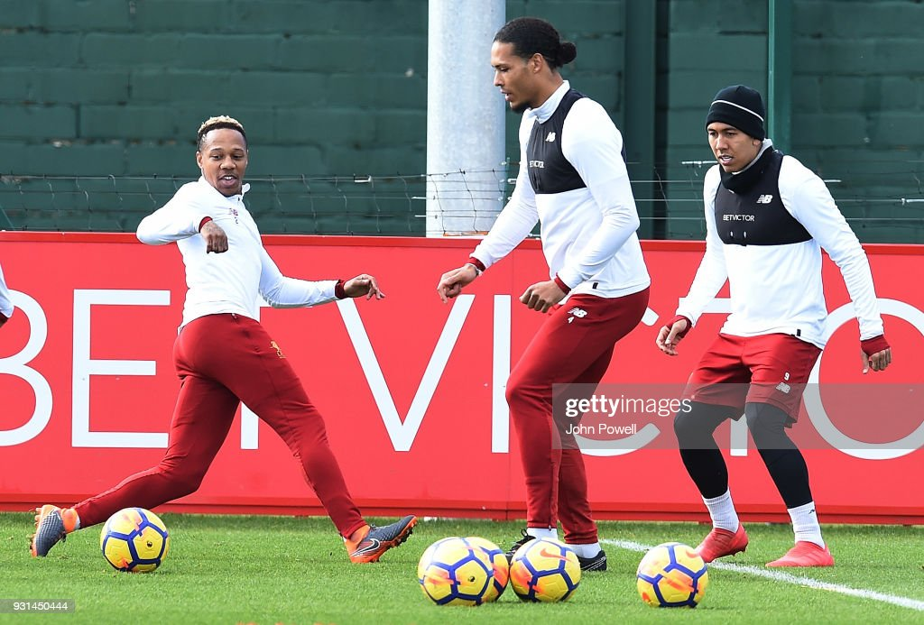 Nathaniel Clyne with Virgil van Dijk and Roberto Firmino of Liverpool during a training session at Melwood Training Ground on March 13, 2018 in Liverpool, England.