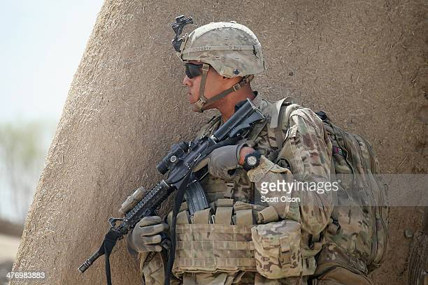 Nathaniel Discosta from Miami Florida with the US Army's 4th squadron 2d Cavalry Regiment keeps watch during a joint patrol through a village with...