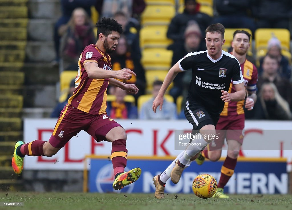 Nathaniel Knight-Percival of Bradford Citymoves forward with the ball watched by Chris Long of Northampton Town during the Sky Bet League One match between Bradford City and Northampton Town at Northern Commercials Stadium, Valley Parade on January 13, 2018 in Bradford, England.
