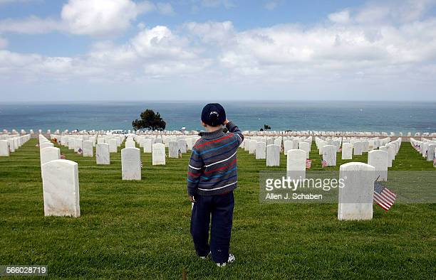 Nathaniel Marley salutes the graves of service men and women as well as his grandpa as he is taught to pay respect and say thank you by his father US...