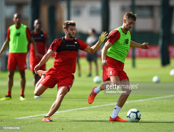 Nathaniel Phillips and Adam Lallana of Liverpool during a training session at Melwood Training Ground on August 21 2018 in Liverpool England