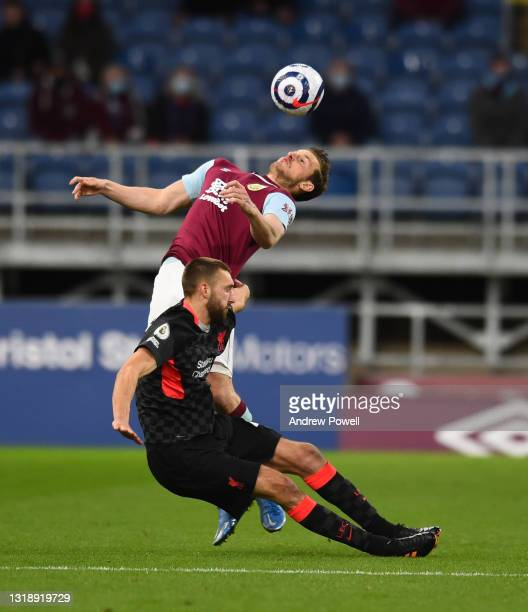 Nathaniel Phillips of Liverpool with Burnley's Chris Wood during the Premier League match between Burnley and Liverpool at Turf Moor on May 19, 2021...