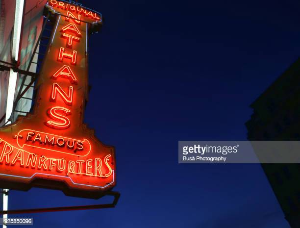 Nathan's Famous Hot Dogs & Restaurants original neon sign along Surf Avenue in Coney Island, Brooklyn, New York, at night