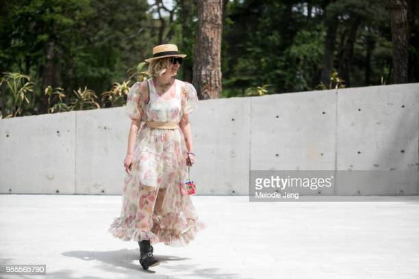 Natia Jguburia wears a sheer floral dress and woven hat at Mercedes-Benz Fashion Week Tbilisi FW18 on May 4, 2018 in Tbilisi, Georgia.