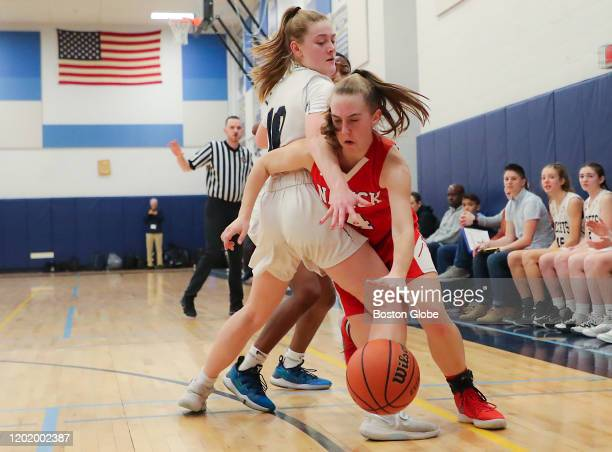Natick High's Emily Gustus drives to the basket with pressure from Needham High's Avery Johnson during first half action of a girl's high school...