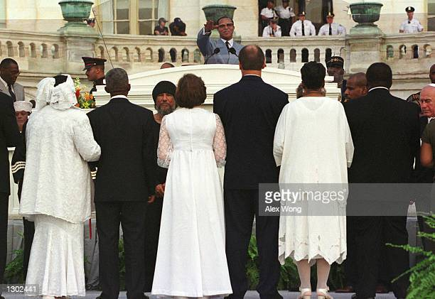 Nation of Islam leader Louis Farrakhan performs a portion of a mass wedding ceremony behind a bulletproof plexiglass shield during the Million Family...