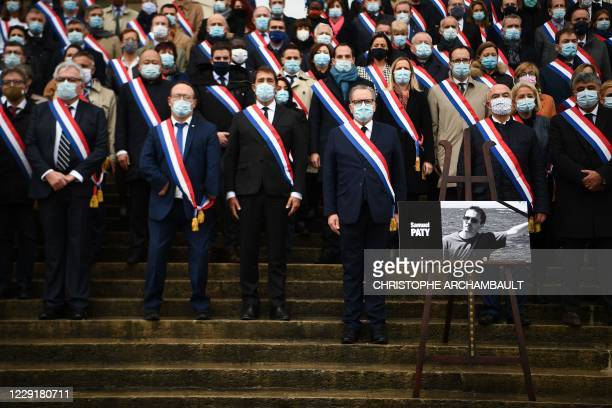 National Assembly president Richard Ferrand stands among French MPs near a photo of late teacher Samuel Paty as they pay tribute on October 20 in...