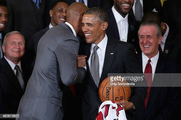 National Basketball Association 2012-2013 champion Miami Heat players Ray Allen embraces President Barack Obama after presenting him with a jersey...