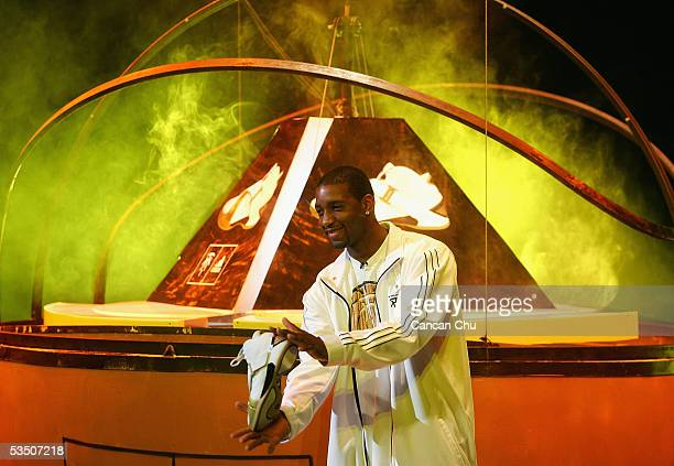 National Basketball Association star player Tracy McGrady of the Houston Rockets displays a shoe during a ceremony to launch an Adidas shoe on August...