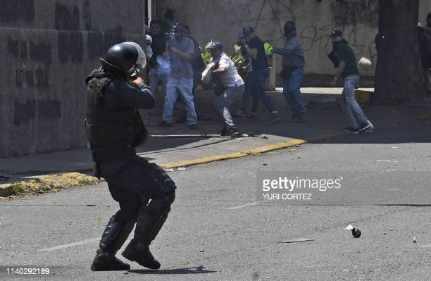 A National Bolivarian Police officer loyal to Venezuelan President Nicolas Maduro confronts demonstrators after troops joined opposition leader Juan...