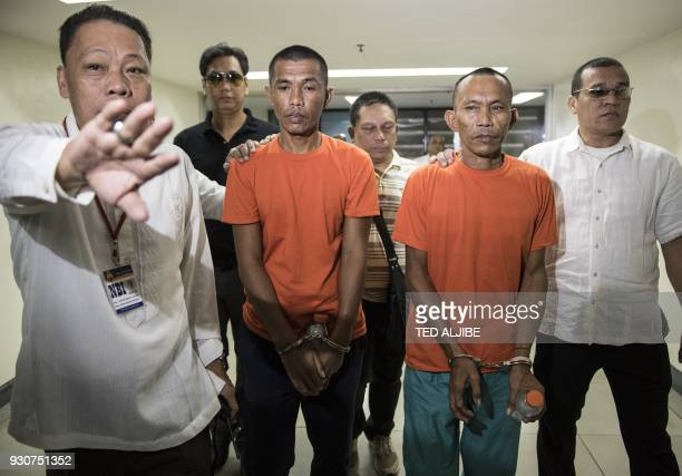 National Bureau of Investigations agents escort suspected Islamist militants Hood Abdullah and Jimmy Bla to a press conference at the National Bureau...